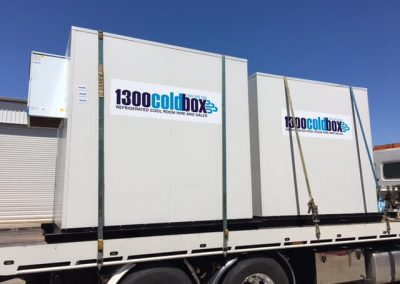 2 coolrooms that are hired being delivered on a truck